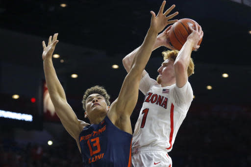 Illinois forward Benjamin Bosmans-Verdonk (13) defends against Arizona guard Nico Mannion during the second half of an NCAA college basketball game Sunday, Nov. 10, 2019, in Tucson, Ariz. Arizona defeated Illinois 90-69. (AP Photo/Rick Scuteri)