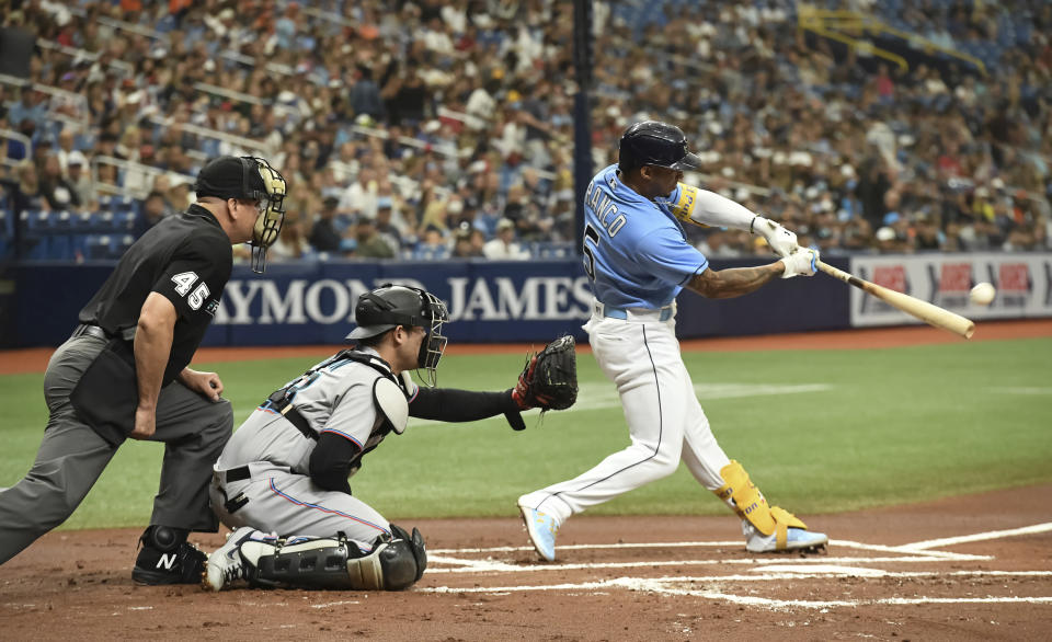 Home plate umpire Jeff Nelson (45) and Miami Marlins catcher Alex Jackson, center, look on as Tampa Bay Rays' Wander Franco (5) hits a double during the first inning of a baseball game Sunday, Sept. 26, 2021, in St. Petersburg, Fla. Franco extended his on-base consecutive game streak to 41. (AP Photo/Steve Nesius)
