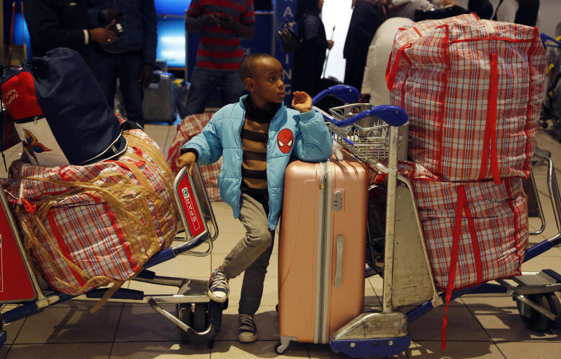 A Nigerian child sits with the family luggage as Nigerian people queue at passport control at the O.R. Tambo International Airport in Johannesburg, South Africa, Wednesday, Sept. 11, 2019. A group of Nigerians boarded a free flight from Johannesburg to Lagos on Wednesday, following a week of violence targeting foreigners in South Africa that has stoked tensions between Africa's two largest economies. It was not immediately clear how many people were on board the flight, operated by the private Nigerian airline Air Peace, but Nigeria's government said it estimated 313 people would board. (AP Photo/Denis Farrell)