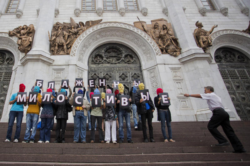 "A security guard at the Christ the Saviour Cathedral, right, runs toward Pussy Riot supporters holding Cyrillic letters reading ""Blessed are The Merciful"" in Moscow, Wednesday, Aug. 15, 2012. The global campaign to free Pussy Riot is gaining speed: Supporters of the punk provocateur band mobilize this week in at least a two dozen cities worldwide to hold simultaneous demonstrations an hour before a Russian court rules on whether its members will be sent to prison. (AP Photo/Novaya Gazeta, Yevgeny Feldman)"