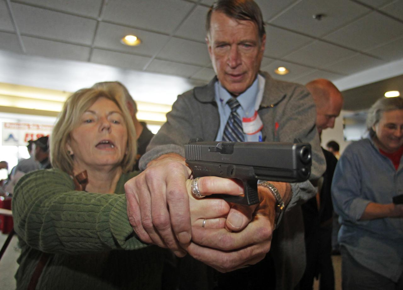 Christine Caldwell, left, receives firearms training with a 9mm Glock from personal defense instructor Jim McCarthy during concealed weapons training for 200 Utah teachers Thursday, Dec. 27, 2012, in West Valley City, Utah. The Utah Shooting Sports Council offered six hours of training in handling concealed weapons in the latest effort to arm teachers to confront school assailants. (AP Photo/Rick Bowmer)
