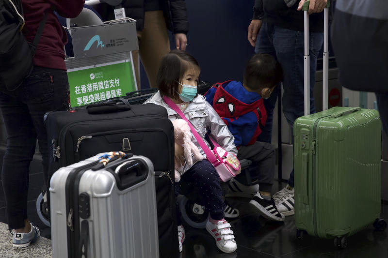 A girl wearing a face mask sits among suitcases at Hong Kong International Airport in Hong Kong, Tuesday, Jan. 21, 2020. Face masks sold out and temperature checks at airports and train stations became the new norm as China strove Tuesday to control the outbreak of a new coronavirus that has reached four other countries and territories and threatens to spread further during the Lunar New Year travel rush. (AP Photo/Ng Han Guan)