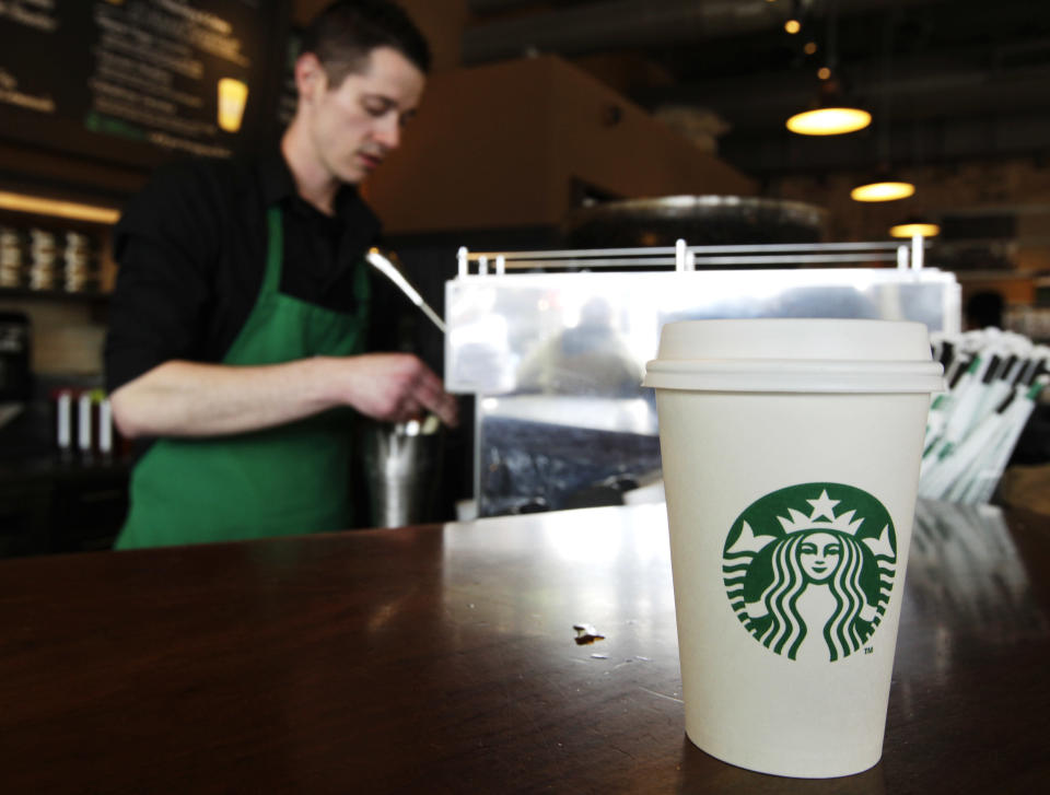 FILE - In this Friday, April 27, 2012, photo, a Starbucks drink waits for a customer to pick it up as barista Josh Barrow prepares another, in Seattle. Starbucks CEO Howard Schultz wants lawmakers to come together to resolve their political gridlock. From Wednesday, Oct. 9, 2013, to Friday, Oct. 11, 2013, the coffee chain is offering a free tall brewed coffee to any customer in the U.S. who buys another person a beverage at Starbucks. (AP Photo/Ted S. Warren, File)