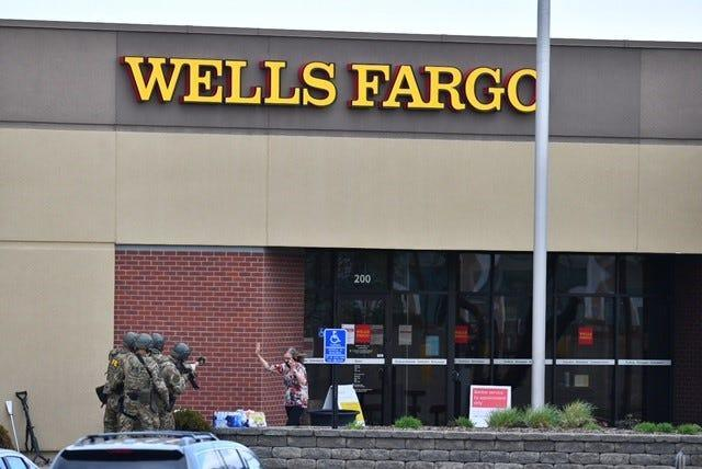 The first female hostage comes out of the Wells Fargo bank building where she had been held for hours, St. Cloud police said.