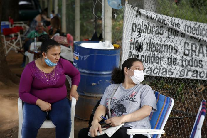 Esther Dominguez, left, and Liz Cristaldo sit outside the ICU of the Respiratory Hospital INERAM where their relatives are being treated for COVID-19 in Asuncion, Paraguay, Wednesday, March 3, 2021, the day after INERAM Director Felipe Gonzalez resigned. Without vaccines or basic drugs to combat COVID-19, Paraguay's main public hospitals became unable to receive patients in intensive care units on Wednesday. (AP Photo/Jorge Saenz)