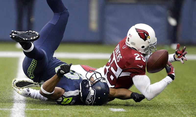 Arizona Cardinals cornerback Jerraud Powers (25) breaks up a pass intended for Seattle Seahawks wide receiver Doug Baldwin in the second half of an NFL football game, Sunday, Dec. 22, 2013, in Seattle. Powers could not hold on for an interception. (AP Photo/Elaine Thompson)