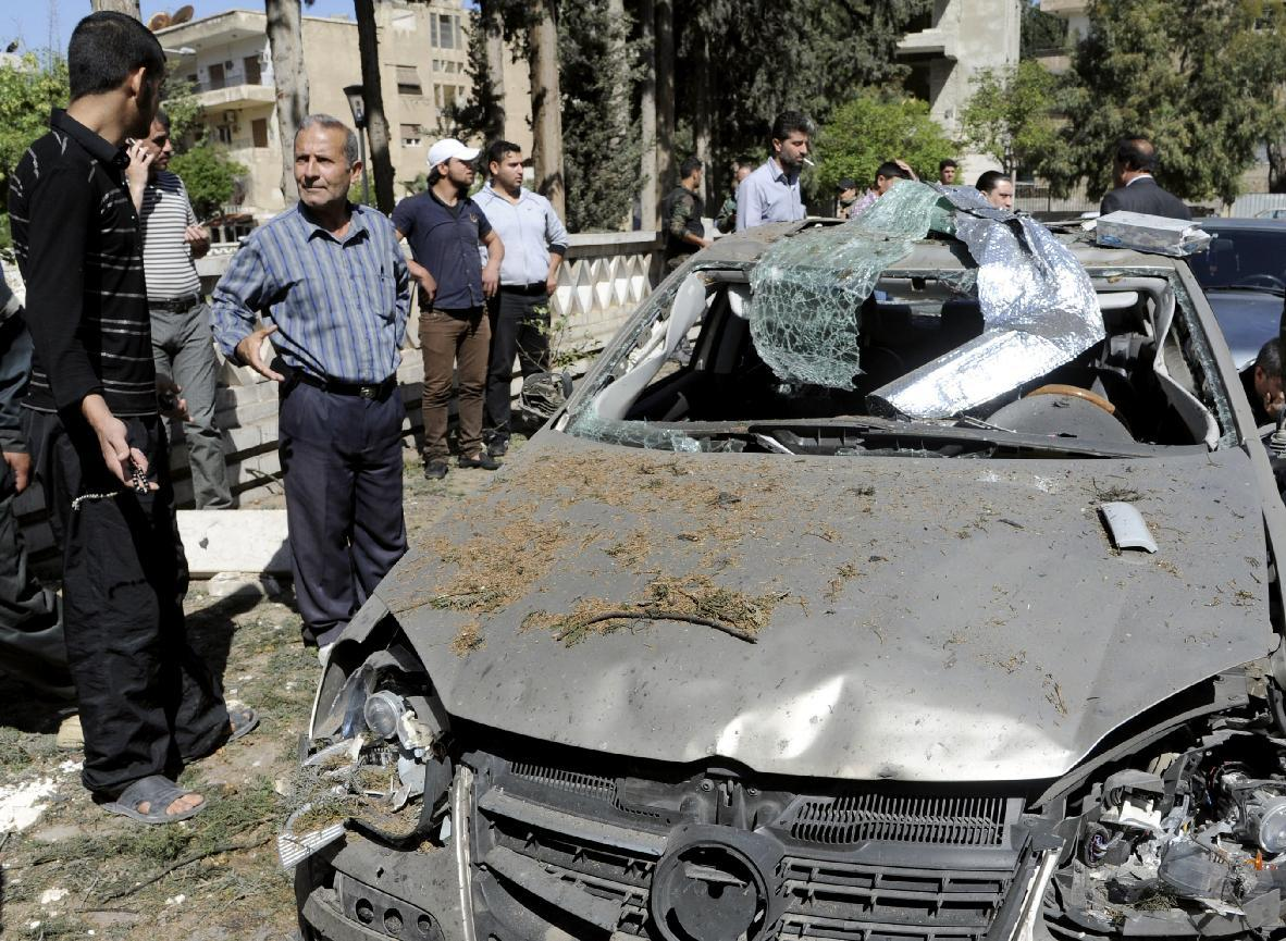 This photo released by the Syrian official news agency SANA, shows Syrians inspecting a damaged car at the scene of a car bomb exploded in the capital's western neighborhood of Mazzeh, in Damascus, Syria, Monday, April. 29, 2013. State-run Syrian TV says the country's prime minister has escaped an assassination attempt when a bomb went off near his convoy. The TV says Prime Minister Wael al-Halqi was unhurt in the attack in the capital's western neighborhood of Mazzeh. (AP Photo/SANA)