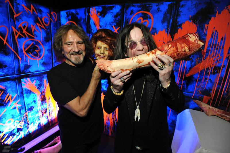 """In this Tuesday, Sept. 17, 2013 photo, Geezer Butler, left, and Ozzy Osbourne pose with props at the """"Black Sabbath: 13 3D"""" maze at Universal Studios Halloween Horror Nights, in Universal City, Calif. While on a behind-the-scenes trek through a Universal Studios Hollywood attraction based on the recently released Black Sabbath album """"13,"""" Osbourne spots a bloody mannequin corpse reclining on a phony altar. Without hesitating, the gruesomely theatrical Sabbath frontman leans down and acts like he's devouring the blood from the decapitated body. (Photo by John Shearer/Invision/AP)"""