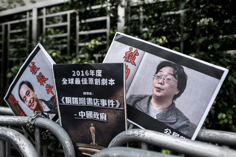 Placards showing missing bookseller Lee Bo (left) and his associate Gui Minhai (right) are left outside the China liaison office in Hong Kong following a January 2016 protest (AFP Photo/Philippe LOPEZ)