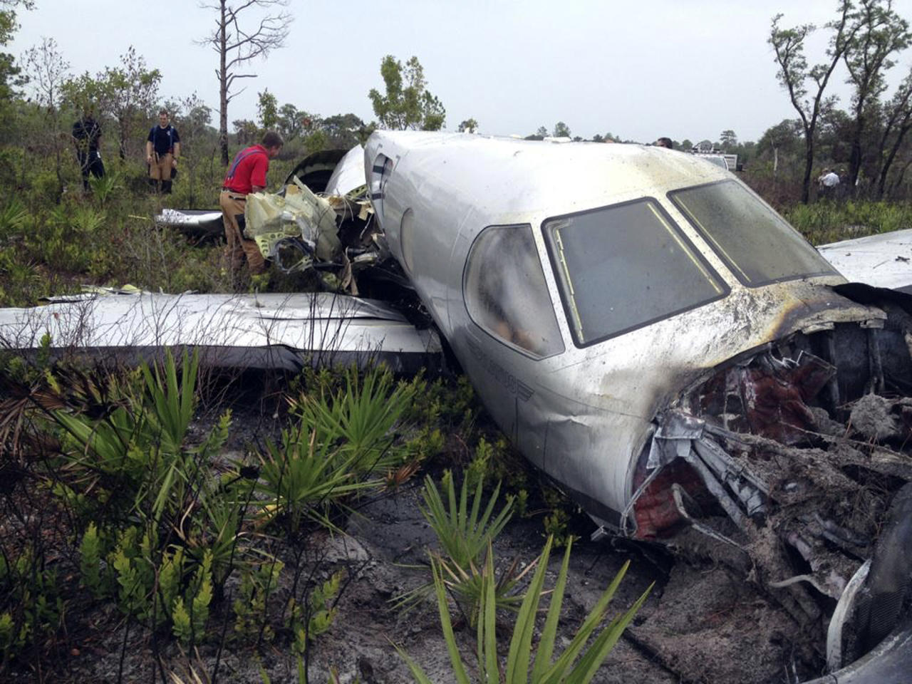 In this photo provided by the Polk County Sheriff's Office, emergency personnel investigate the site where a Pilatus PC-12, a single-engine turboprop passenger plane, crashed near Lake Weohyakapka, aka Lake Walk In the Water, in southeast Polk County, Fla. on Thursday, June 7, 2012. Ronald Bramlage, 45, of Junction City, Kan., who was piloting the plane, his wife Rebecca and their four children were killed in the crash. (AP Photo/Polk County Sheriff's Office)