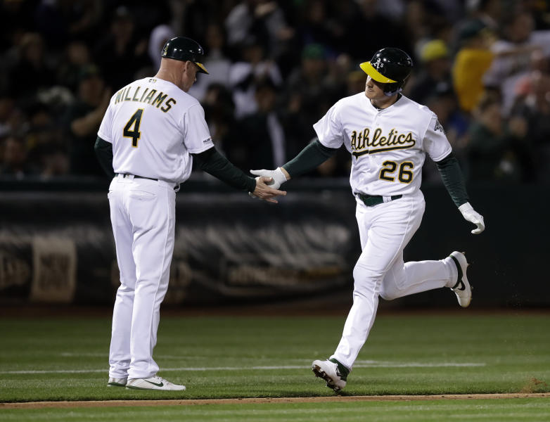Oakland Athletics' Matt Chapman, right, is congratulated by third base coach Matt Williams after hitting a home run against the Houston Astros during the sixth inning of a baseball game Wednesday, April 17, 2019, in Oakland, Calif. (AP Photo/Ben Margot)
