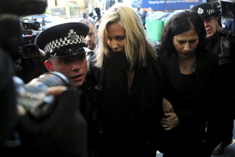 """FILE - In this file photo dated Monday, Dec. 23, 2019, Love Island TV presenter Caroline Flack, centre, is escorted by police as she arrives at court in London, after being charged with assault of former professional tennis player and model Burton. The host of controversial reality TV show """"Love Island,"""" has died aged 40, according to a statement from her family Saturday Feb. 15, 2020. (AP Photo/Petros Karadjias, FILE)"""