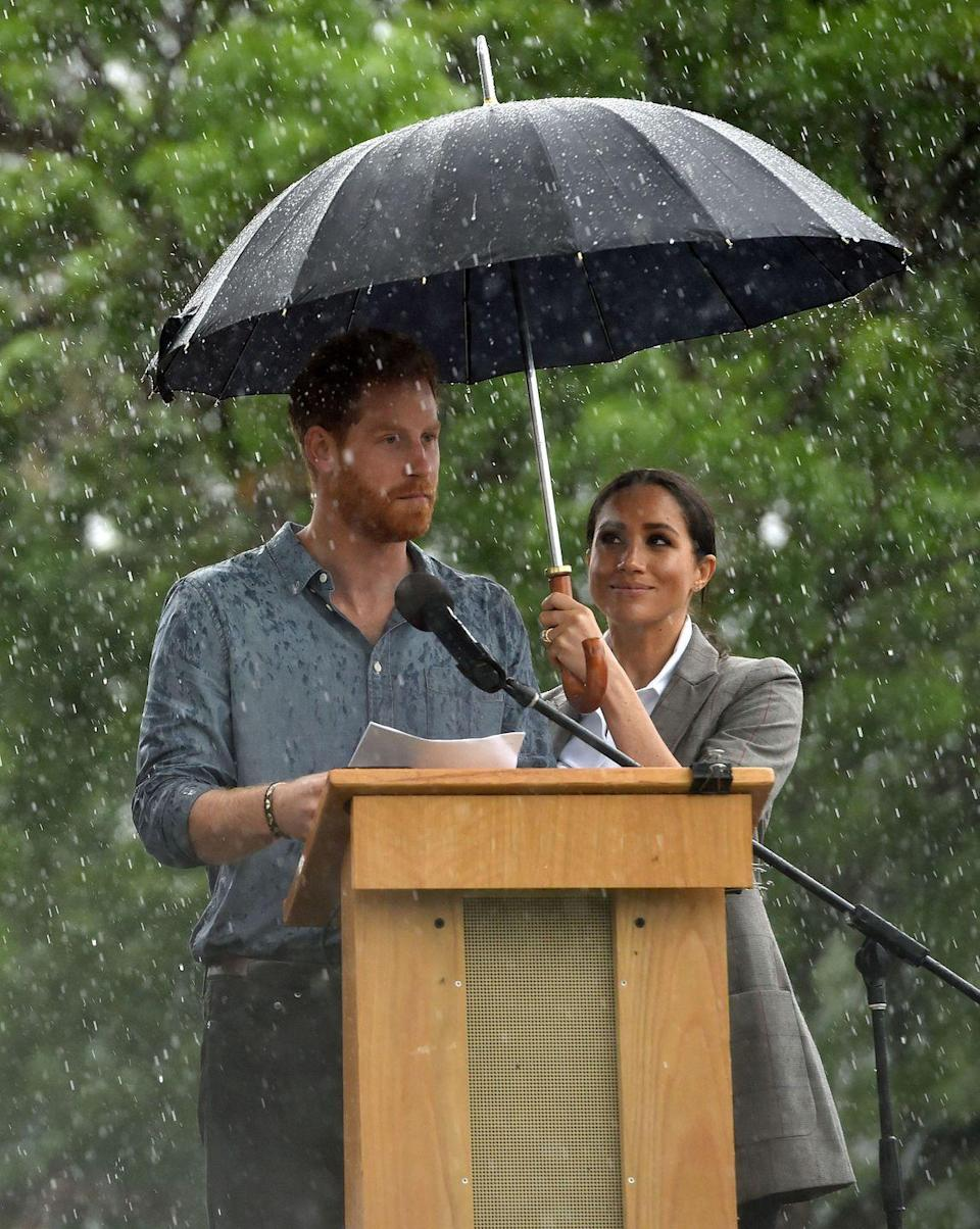 <p>The Duchess of Sussex adorably held an umbrella over her husband's head as he presented at speech during their visit to Dubbo, Australia. </p>