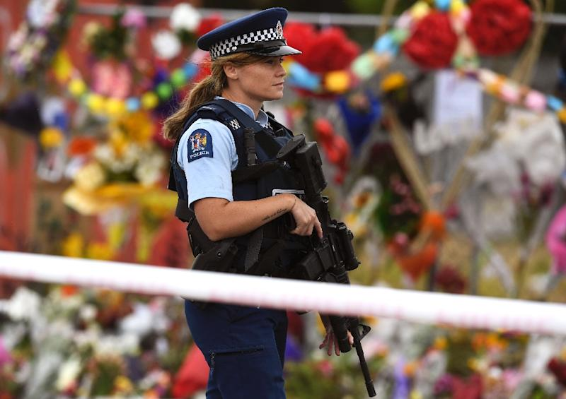 A policewoman patrols past a memorial wall outside the Linwood Mosque in Christchurch on Thursday (AFP Photo/WILLIAM WEST)