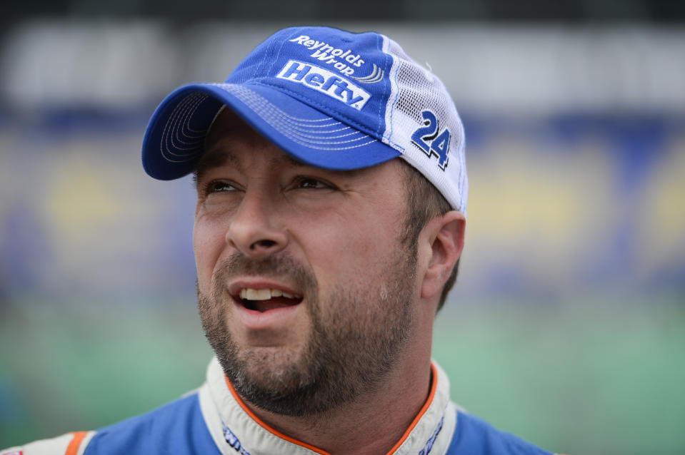 Eric McClure, driver of the #24 Reynolds Wrap Toyota, stands in the garage area during qualifying for the NASCAR XFINITY Series Kansas Lottery 300 at Kansas Speedway on October 17, 2015 in Kansas City, Kansas.