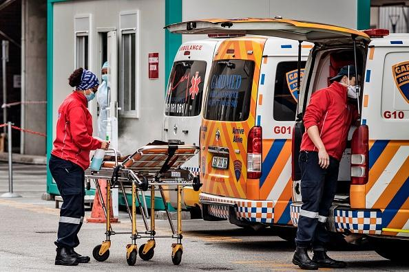 A member of an ambulance crew sanitises a gurney at the emergencies of the Greenacres Hospital in Port Elizabeth, South Africa, near a line of queuing ambulances.
