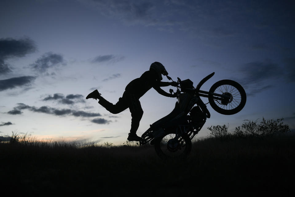 """Stuntman Pedro Aldana performs a wheelie on his motorcycle during an exhibition in the Ojo de Agua neighborhood of Caracas, Venezuela, Sunday, Jan. 10, 2021. The motorcycle trick rider and adrenalin junkie who prefers the nickname """"Crazy Pedro,"""" draws masses of Venezuelans starved for entertainment to his shows across the country. (AP Photo/Matias Delacroix)"""