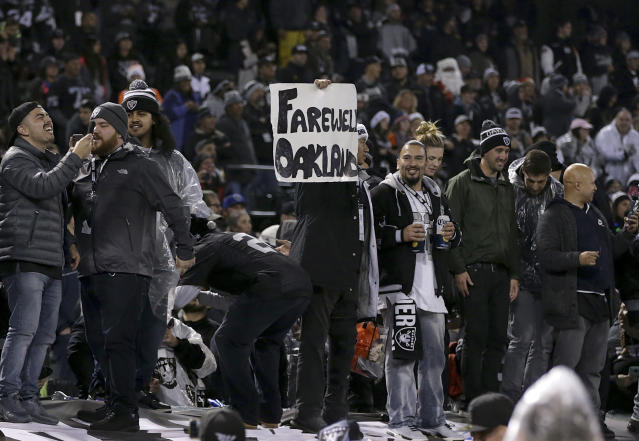 A fan holds up a sign while standing on a dugout at Oakland-Alameda County Coliseum after the final Raiders game at the stadium. (AP)