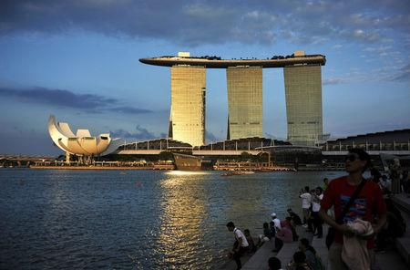 FILE PHOTO: People sit on the waterfront as sunlight shines on the Marina Bay Sands integrated resort during dusk in downtown Singapore