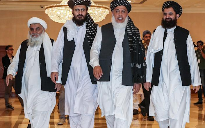(FILES) In this file photo taken on July 8, 2019, Mohammad Nabi Omari (C-L), a Taliban member formerly held by the US at Guantanamo Bay and reportedly released in 2014 in a prisoner exchange, Taliban negotiator Abbas Stanikzai (C-R), and former Taliban intelligence deputy Mawlawi Abdul Haq Wasiq (R) walk with another Taliban member during the second day of the Intra Afghan Dialogue talks in the Qatari capital Doha