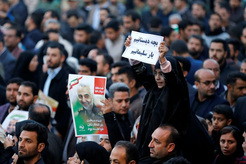 A girl holds a sign during a funeral procession for Soleimani and al-Muhandis, in Ahvaz
