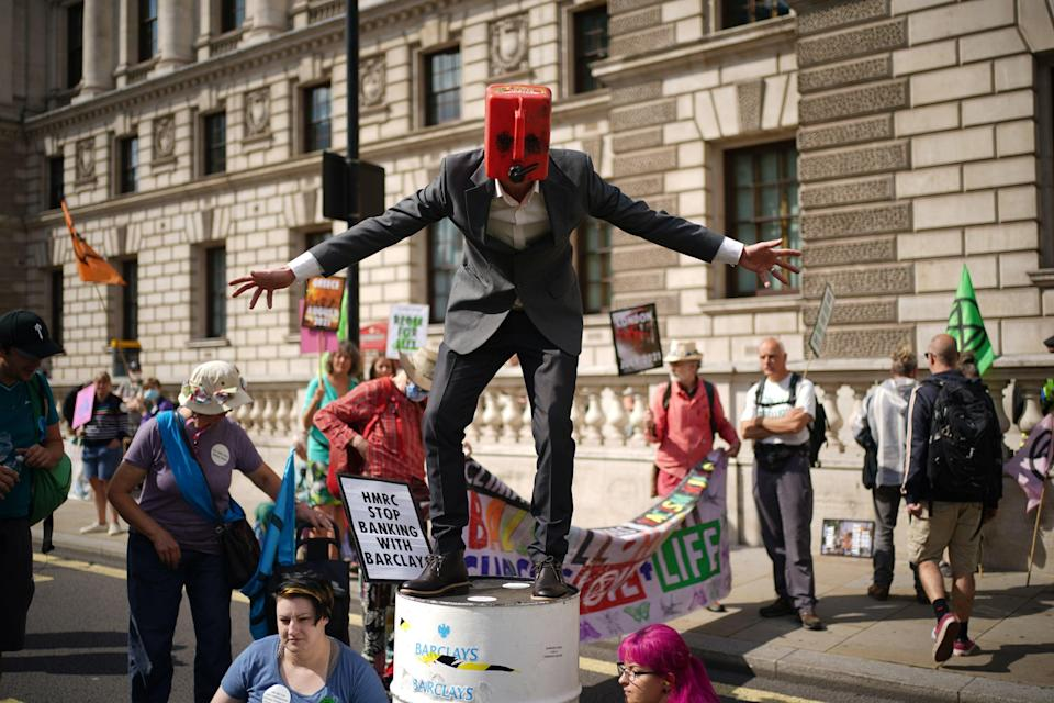 A man wearing a petrol on top of a barrel joins climate activists from XR during a protest outside the offices of HM Revenue and Customs (HMRC) (PA)