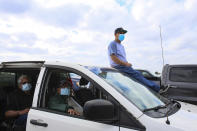 Delfino Reyes sits on the roof of the van as he and three seniors from La Esperanza Adult Day Care Center wait to move up in line Friday, Jan. 29, 2021, for the COVID-19 vaccine clinic at the Los Fresnos Fire Station & EMS in Los Fresnos, Texas.(Denise Cathey/The Brownsville Herald via AP)