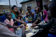 Paska Itwari Beda, the young mother of five children, shares a meal with her family at her Juba, South Sudan home, Thursday, May 27, 2021. The young mother of five children - all of them under age 10 - sometimes survives on one bowl of porridge a day, and her entire family is lucky to scrape together a single daily meal, even with much of the money Beda makes cleaning offices going toward food. (AP Photo/Adrienne Surprenant)