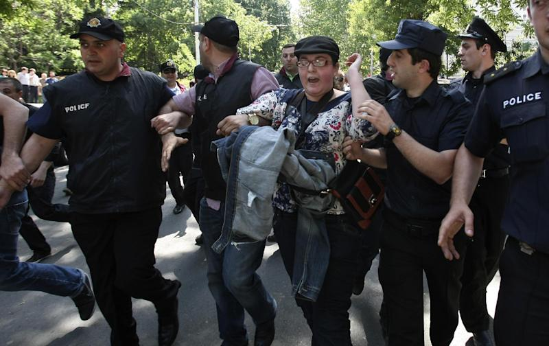 Police officers guard a gay activist who arrived for a gay pride rally to a bus to take her out of the city center in Tbilisi, Georgia, Friday, May 17, 2013. Thousands of anti-gay protesters, including Orthodox priests, occupied a central street in Georgia's capital Friday, with some threatening to lash with nettles any participant in a gay pride parade which was to take place there. Police in Tbilisi guarded several dozen gay activists and bused them out of the city center shortly after they arrived at the gathering. (AP Photo/Shakh Aivazov)