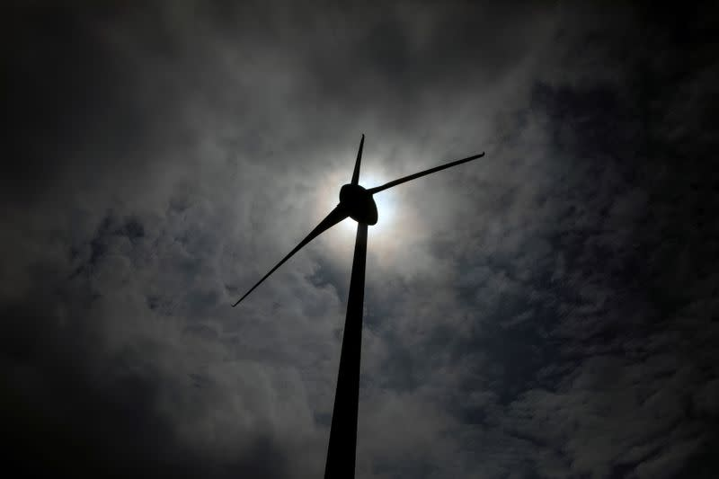 FILE PHOTO: A wind turbine is silhouetted on a mountain on the island of Evia