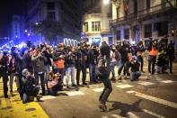 Media take images as a man throws a bottle against a national police station during clashes following a protest condemning the arrest of rap singer Pablo Hasel in Barcelona, Spain, Sunday, Feb. 21, 2021. The imprisonment of Pablo Hasel for inciting terrorism and refusing to pay a fine after having insulted the country's monarch has triggered a social debate and street protests. (AP Photo/Emilio Morenatti)