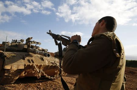 An Israeli soldier unloads his weapon near the border with Lebanon January 29, 2015. REUTERS/Baz Ratner