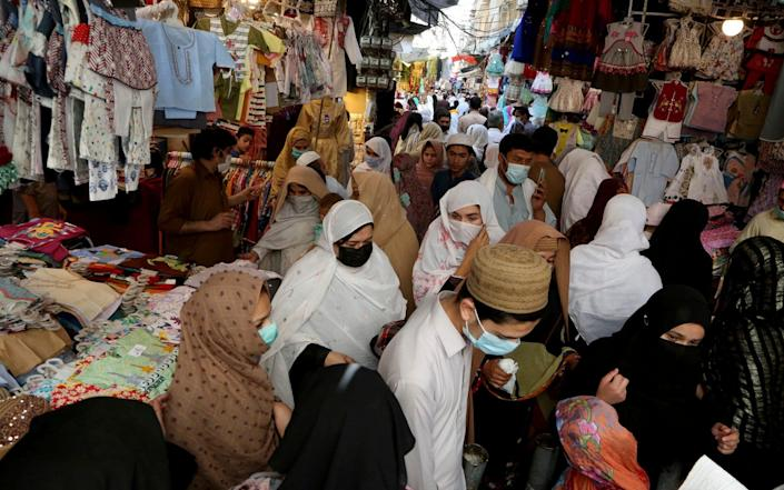 People ignore social distancing while shopping at a market after the government announced new restrictions to help control the spread of the coronavirus, in Peshawar, Pakistan - Muhammad Sajjad/AP