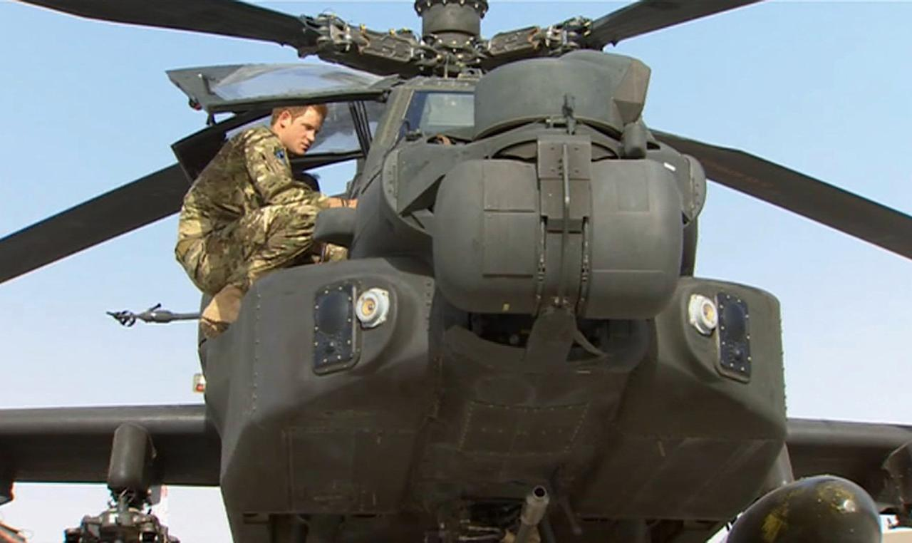 In this image from video, Britain's Prince Harry is shown an Apache helicopter by a member of his squadron, obscured behind, (name not provided) at Camp Bastion in Afghanistan, Friday Sept. 7, 2012. Prince Harry will be based at Camp Bastion during his tour of duty as a co-pilot gunner, returning to Afghanistan to fly attack helicopters in the fight against the Taliban. (AP Photo/TV Pool)