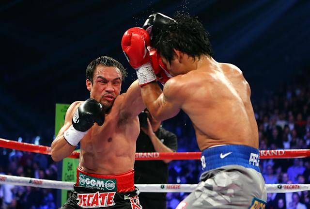 LAS VEGAS, NV - DECEMBER 08: (L-R) Juan Manuel Marquez throws a left at Manny Pacquiao during their welterweight bout at the MGM Grand Garden Arena on December 8, 2012 in Las Vegas, Nevada. (Photo by Al Bello/Getty Images)
