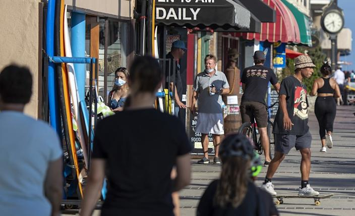 """People walk and skateboard on the sidewalk past businesses on July 20 in Newport Beach. Orange County reported 31 new COVID-19 deaths Saturday. <span class=""""copyright"""">(Allen J. Schaben / Los Angeles Times)</span>"""