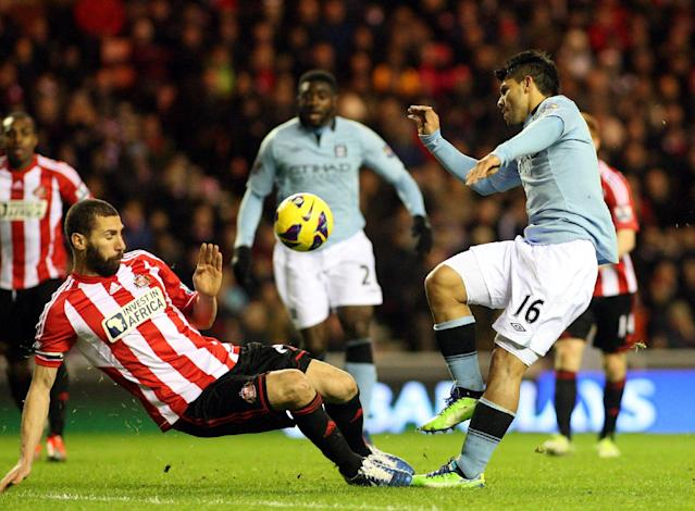 FILE - This is a Wednesday Dec. 26, 2012 file photo of Manchester City's Sergio Aguero, right, as he has a shot towards the goal goal Sunderland's captain Carlos Cuella, left, during their English Premier League soccer match at the Stadium of Light, Sunderland, England. With their six-figure weekly salaries, flashy cars, plush houses and supermodel wives and girlfriends, sympathy is usually in short supply when it comes to footballers in the lucrative English Premier League. Except, maybe, over the Christmas and New Year period. When you are tucking into your big turkey dinner, knocking back the red wine and spending time with the family over the festive period, spare a thought for the likes of Wayne Rooney, Steven Gerrard and Sergio Aguero this Christmas.(AP Photo/Scott Heppell, File)