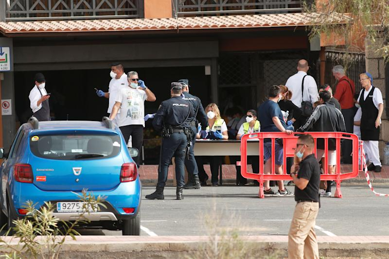 Emergency workers rest at a health control outside of H10 Hotel, which is on lockdown after novel coronavirus has been confirmed in Adeje, on the Spanish island of Tenerife, Spain.