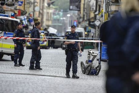 Policemen and a bomb robot are seen in a cordoned-off area in the old town of central Stockholm