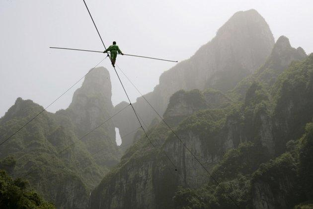 Samat Hasan, a 24-year-old stuntman from Xinjiang Uighur Autonomous Region, walks on a tightrope in Zhangjiajie, Hunan province April 25, 2009. Walking on a 700-metre-long (2,300 ft) rope with a 3.1-centimetre (1.2 inches) diameter and set at a 39-degree gradient, Hasan successfully broke the Guinness World Record for aerial tightrope walking after failing in a previous attempt in October last year, local media reported. REUTERS/China Daily