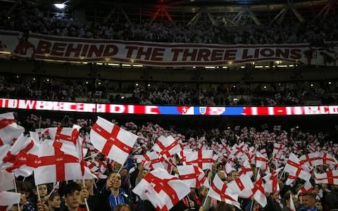England's supporters wave flags during the playing of the national anthem ahead of the UEFA Euro 2020 Group A qualification football match between England and Czech Replublic at Wembley Stadium in London on March 22, 2019 - Credit: AFP