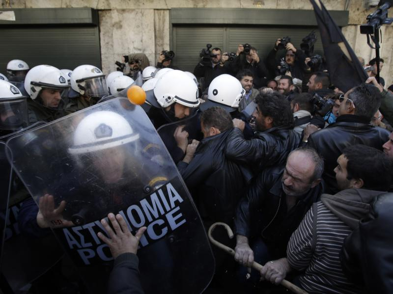 Farmers clash with riot police outside Greece's parliament in Athens on Friday, Dec. 20, 2013. Farmers from the island of Crete clashed with police as lawmakers prepared to vote on a new property tax that will extend the levy to include farms. (AP Photo/Thanassis Stavrakis)