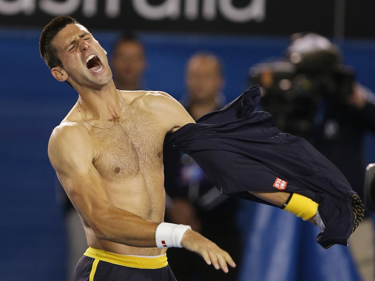 Serbia's Novak Djokovic rips his shirt off as he celebrates his fourth round win over Switzerland's Stanislas Wawrinka at the Australian Open tennis championship in Melbourne, Australia, Monday, Jan. 21, 2013. (AP Photo/Dita Alangkara)