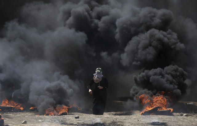 <p>A Palestinian woman walks through black smoke from burning tires during a protest on the Gaza Strip's border with Israel, May 14, 2018. (Photo: Khalil Hamra/AP) </p>