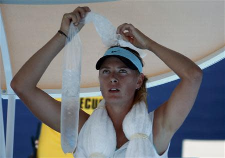 Maria Sharapova of Russia holds ice on her head during her women's singles match against Karin Knapp of Italy at the Australian Open 2014 tennis tournament in Melbourne January 16, 2014. REUTERS/David Gray