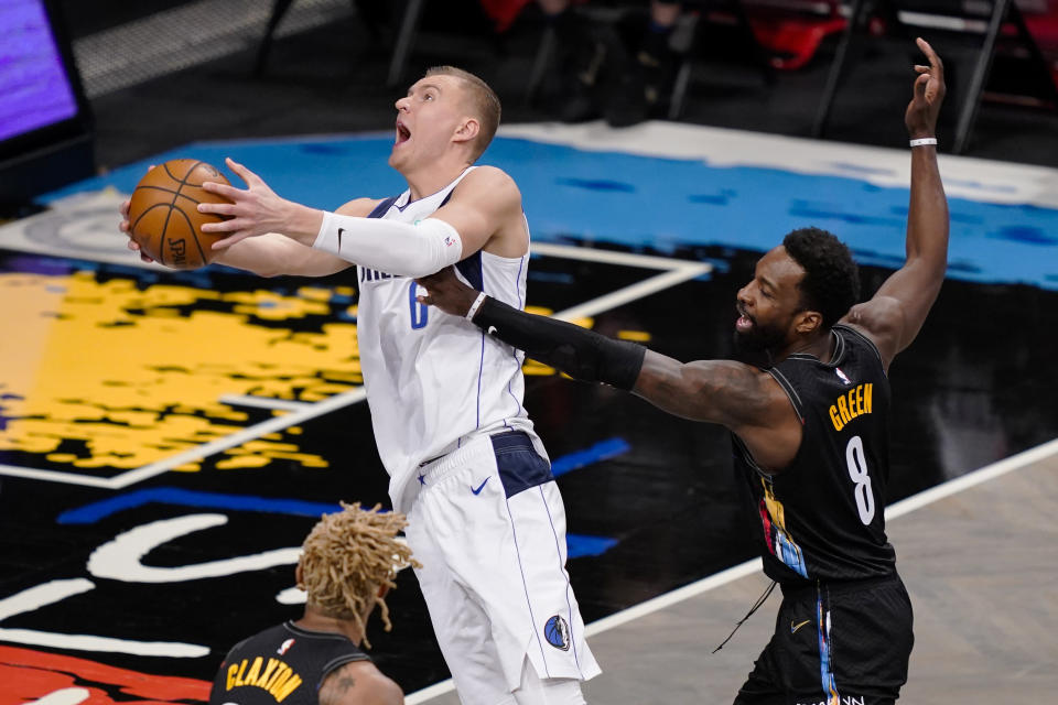 Dallas Mavericks center Kristaps Porzingis (6) shoots against Brooklyn Nets forward Jeff Green (8) during the second half of an NBA basketball game Saturday, Feb. 27, 2021, in New York. (AP Photo/John Minchillo)