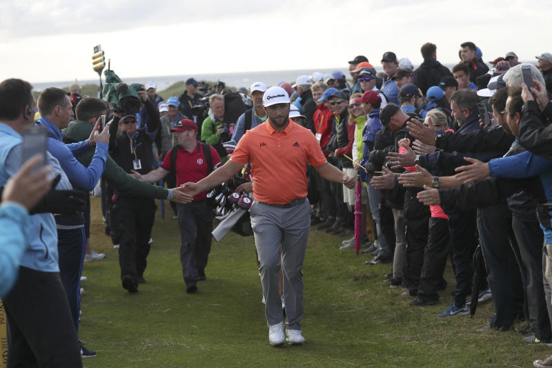 Spain's Jon Rahm reaches out and touches the hands of spectators as he walks to 17th tee during the first round of the British Open Golf Championships at Royal Portrush in Northern Ireland, Thursday, July 18, 2019.(AP Photo/Peter Morrison)