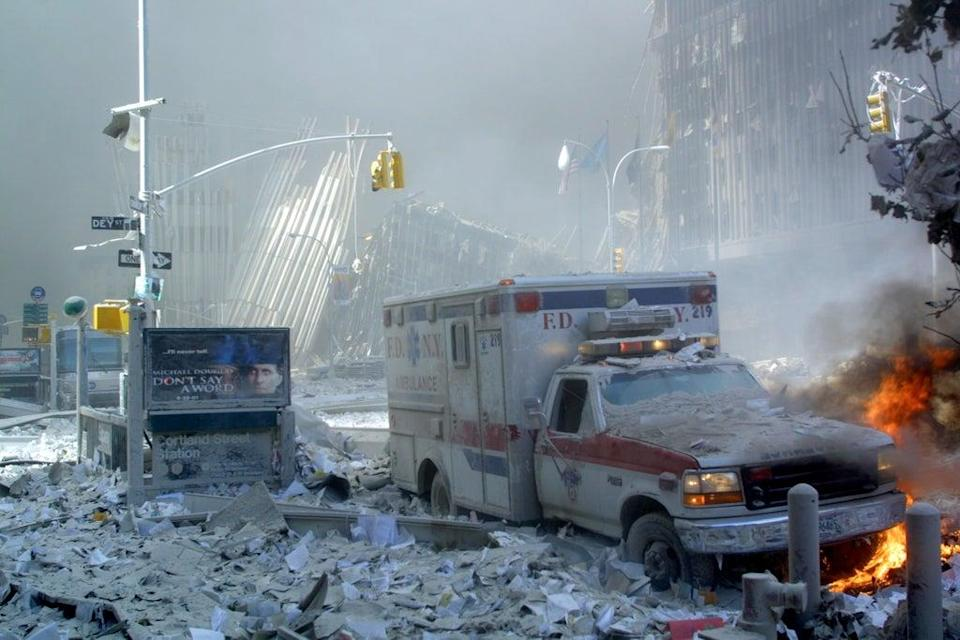 An ambulance, covered with debris and on fire, after the collapse of the first tower (AFP/Getty)