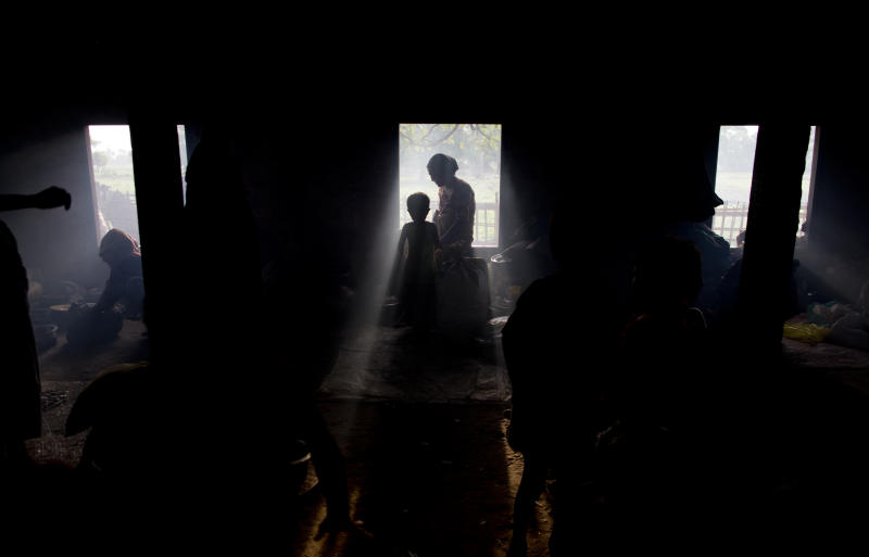 Internally displaced Rohingya people taking refuge in a building belongs to a mosque are silhouetted in Sittwe, northwestern Rakhine State, Myanmar, ahead of the arrival of Cyclone Mahasen, Wednesday, May 15, 2013. A massive evacuation to clear low-lying camps ahead of a cyclone has run into a potentially deadly snag as members of the displaced Rohingya minority living there have refused to leave because they don't trust Myanmar authorities. (AP Photo/Gemunu Amarasinghe)