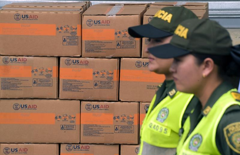 Colombian policewomen walk past boxes with US humanitarian aid goods in Cucuta, Colombia, on the border with Tachira, Venezuela, on February 8, 2019 (AFP Photo/Raul ARBOLEDA)